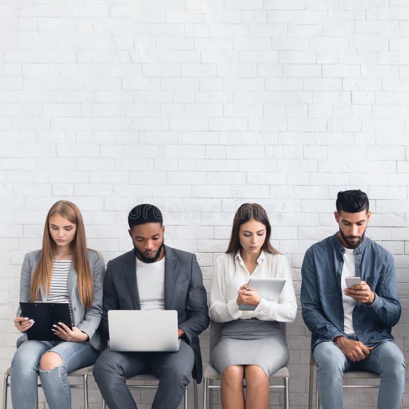Candidatos que esperan entrevistas de trabajo, sentándose en fila imagen de archivo libre de regalías