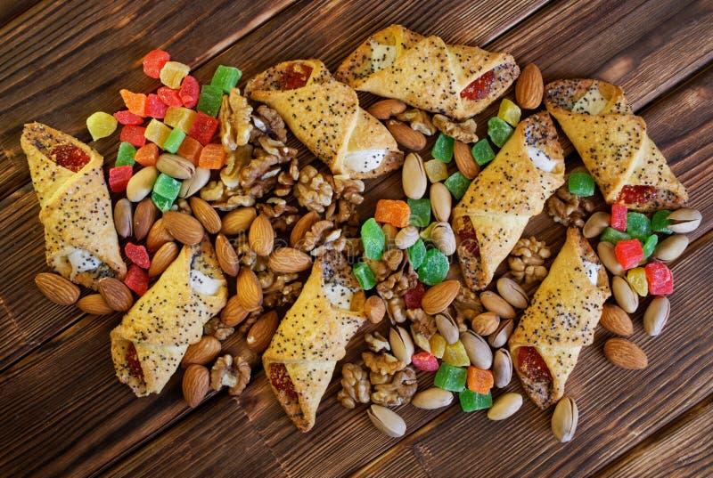 Candied плоды, фисташки, миндалины, грецкие орехи и домодельные печенья с маковыми семененами и вареньем на деревенском деревянно стоковое фото