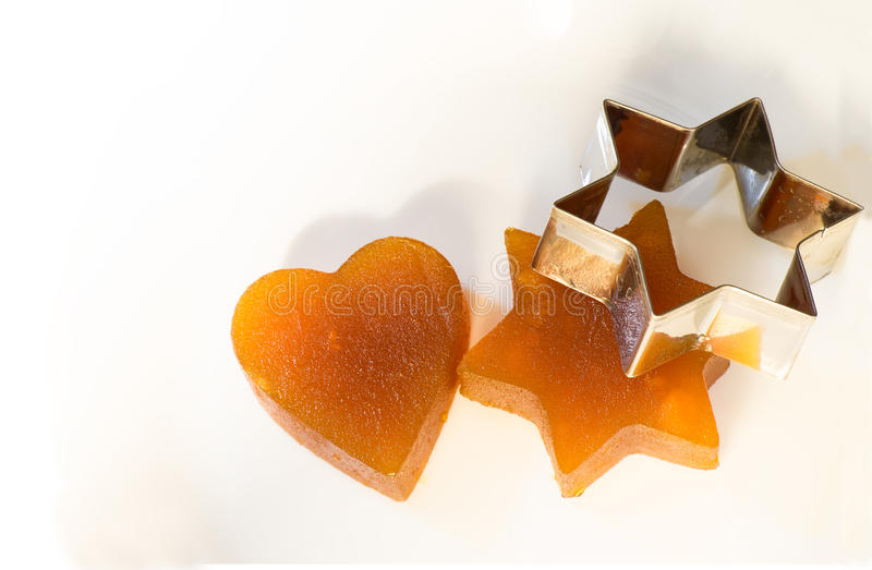 Candied fruit jelly apricot in the form of heart and star of David with iron form royalty free stock photography