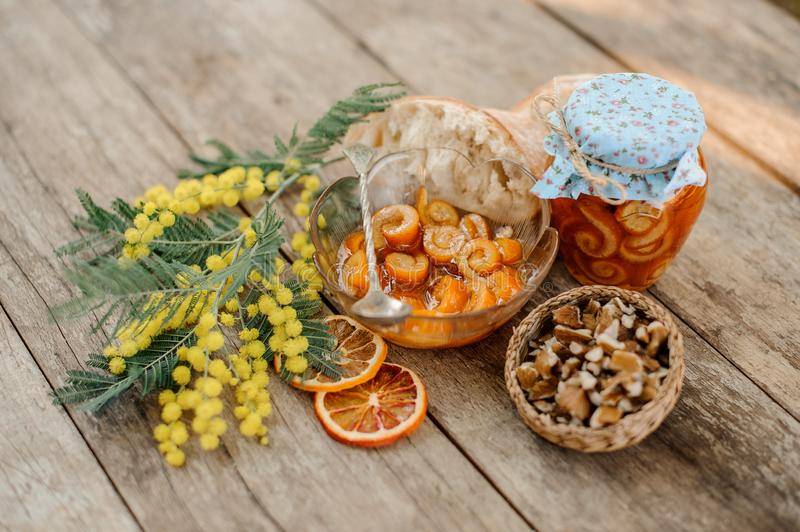 Candied orange spiral peel with sugar syrup in a glass jar and plate near the saucer with walnuts, mimosa and bread royalty free stock image