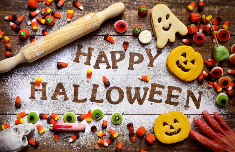 Candies, cookies and text Happy Halloween. High-angle shot of a wooden table sprinkled with icing sugar where you can read the text Happy Halloween, some royalty free stock photography