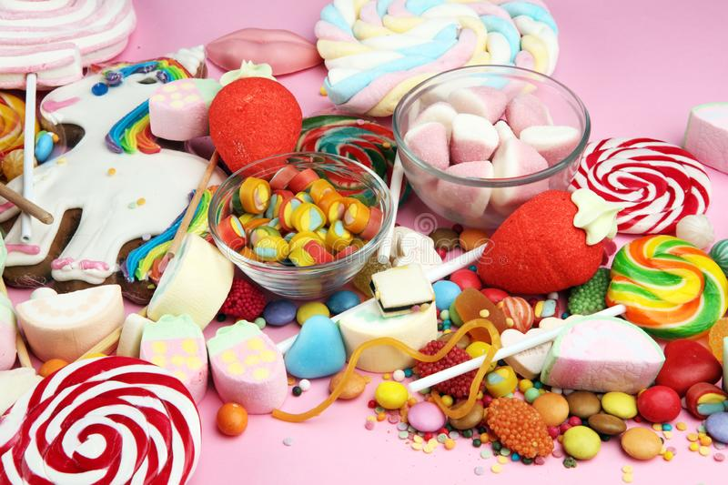 Candies with jelly and sugar. colorful array of different childs sweets and treats on pink stock photo