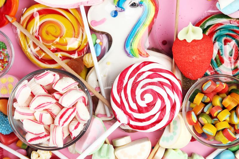 Candies with jelly and sugar. colorful array of different childs sweets and treats on pink stock images
