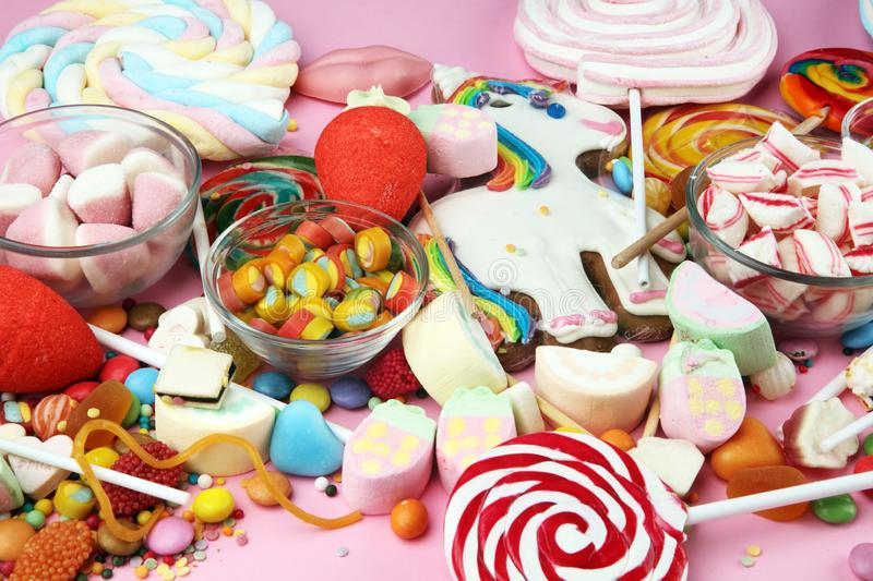 Candies with jelly and sugar. colorful array of different childs sweets and treats on pink royalty free stock photos