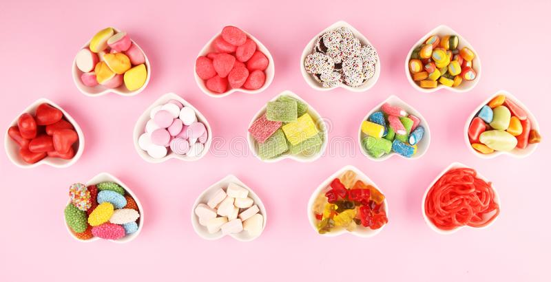 Candies with jelly and sugar. colorful array of different childs sweets and treats on pink background royalty free stock images