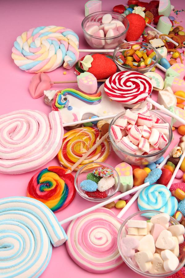 Candies with jelly and sugar. colorful array of different childs sweets and treats on pink royalty free stock photography