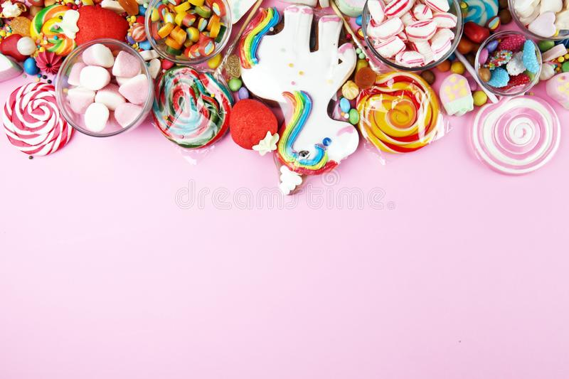 Candies with jelly and sugar. colorful array of different childs sweets and treats on pink royalty free stock image