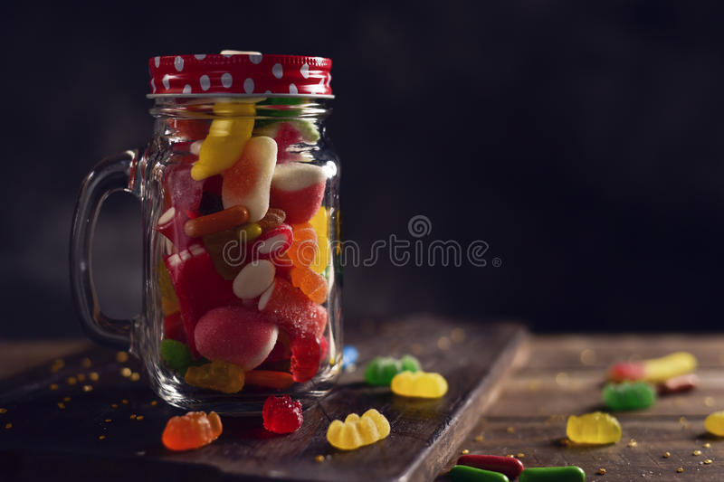 Candies in a mason jar. A mason jar full of candies with different flavors and colors, on a rustic wooden table stock photos