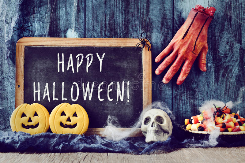 Candies, ornaments and text happy halloween in a chalkboard. A chalkboard with the text happy halloween, placed on a rustic wooden surface next to a skull, some royalty free stock photography