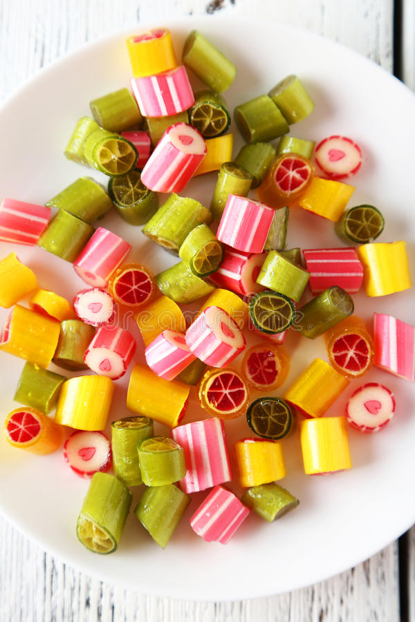 Candies. On plate on white wooden background stock images
