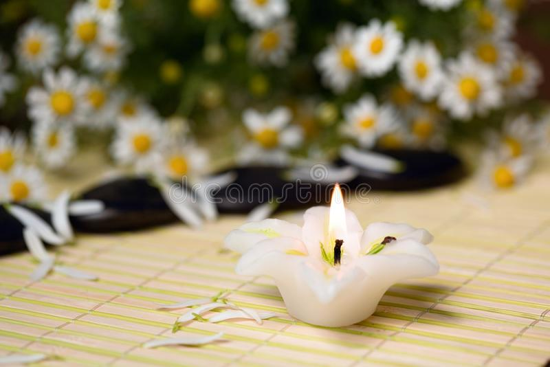 Candle. A burning candle and stones for spa massage royalty free stock image