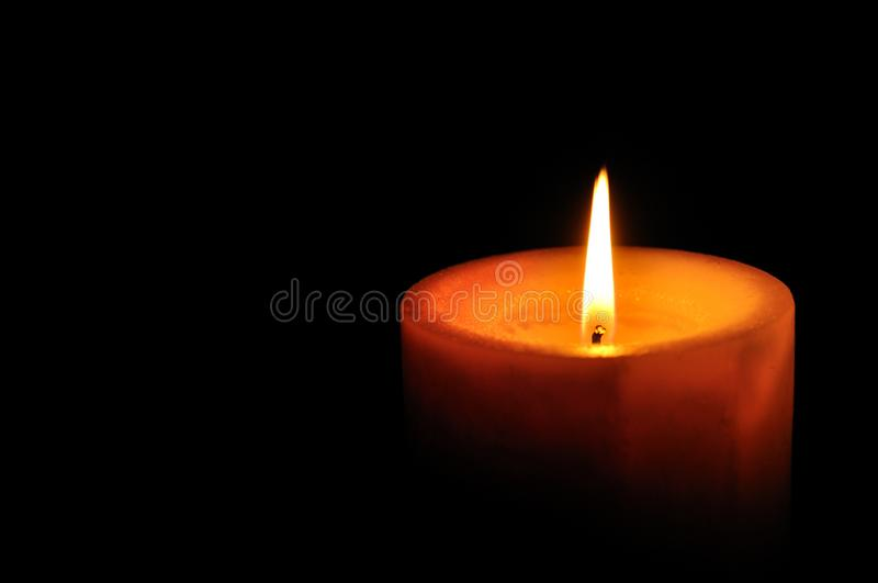 Burning candle. On right of the frame with black background royalty free stock images