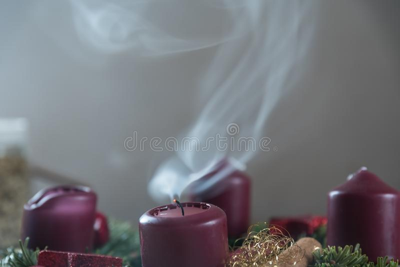 Candle on the Advent wreath goes out. Smoldering Christmas wreath candle goes out and smokes - close up Advent wreath stock photos