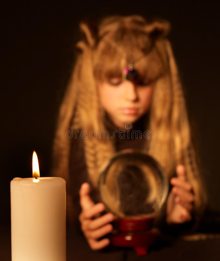 Candle against the girl holding crystal ball.