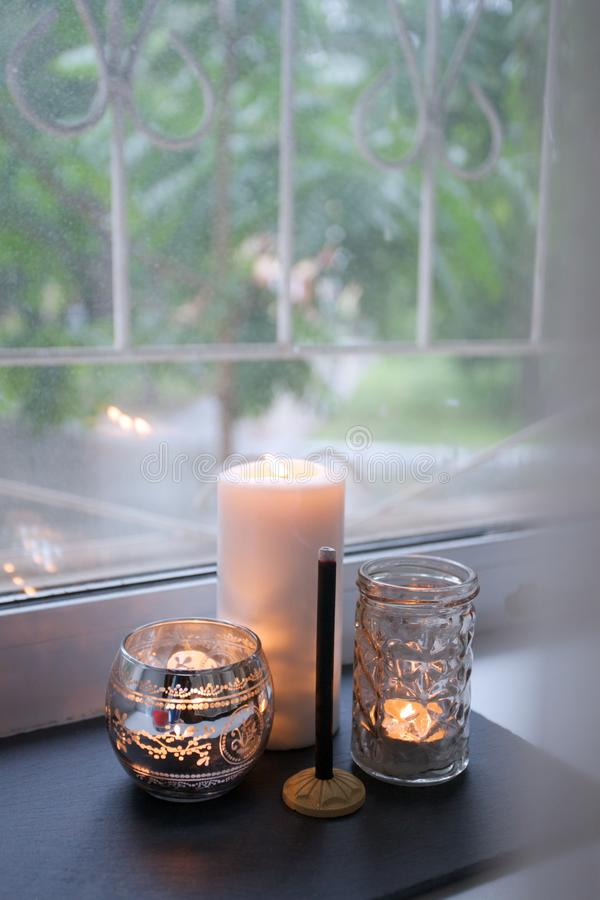 Candle and aroma stick on windowsill. Concept of relax, tranquil, peaceful, unplug, balanced time, Keep kalm and take it easy. Candle and aroma stick on stock photo