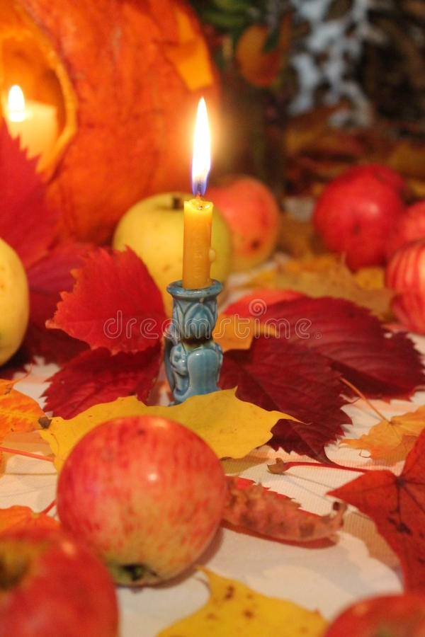 Candle. Beautiful bright burning candle stay on orange, red autumn leaves prepare for celebration autumn holiday royalty free stock photos