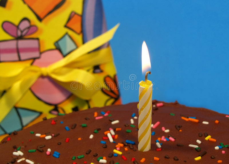 Candle on a birtday cake. Single candle on a chocolate cake (with gift in background royalty free stock photography