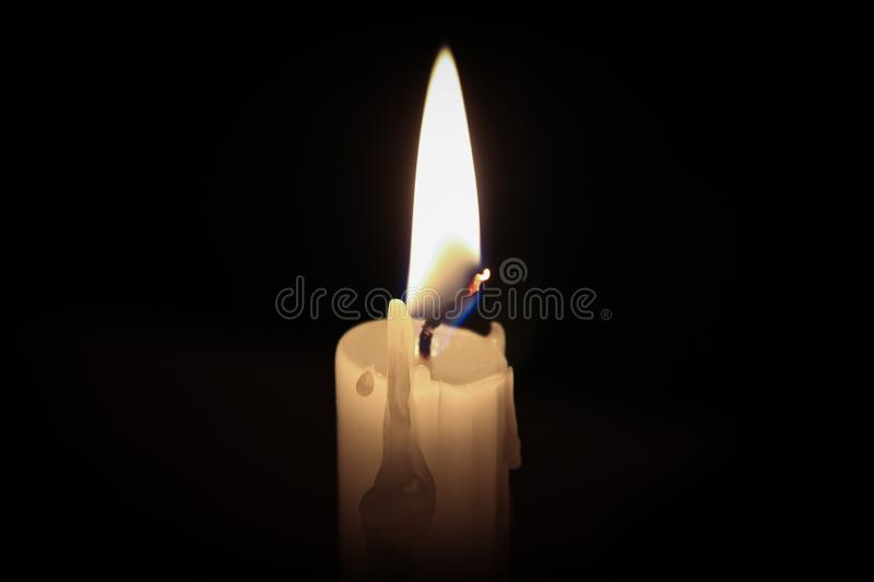 A candle with a black background royalty free stock images