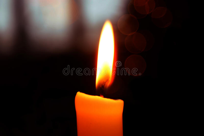 A candle on a black background. stock photos