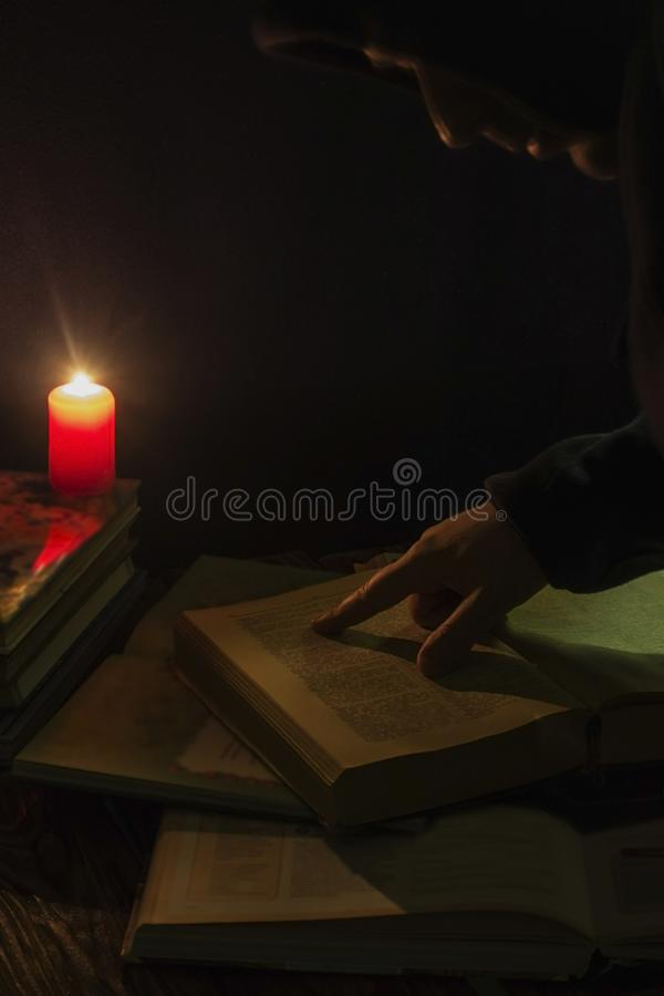 Candle and a book of the Bible on wooden background at night royalty free stock images
