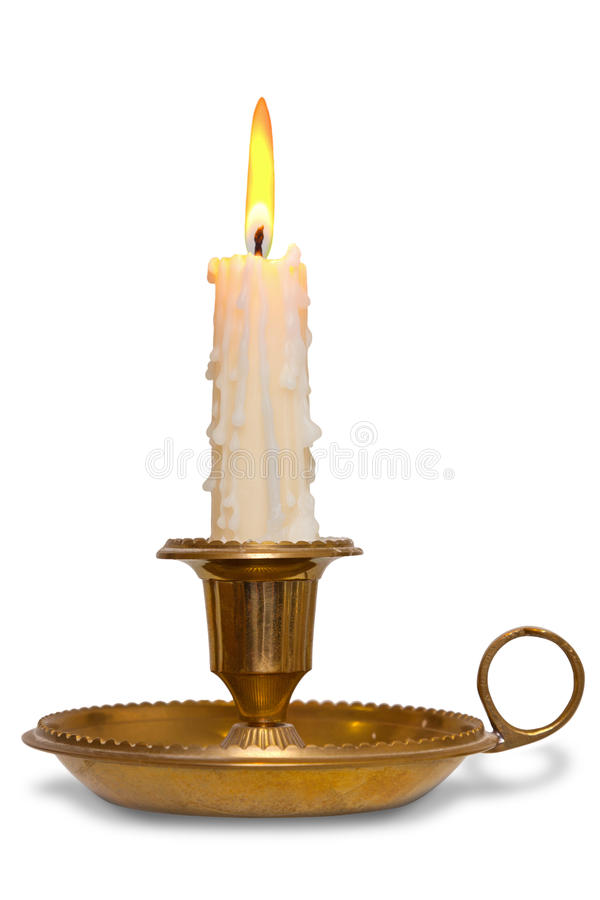 Candle in brass holder. A dripping wax candle burning with flame in a traditional brass holder known as a chamberstick, on a white background royalty free stock photo