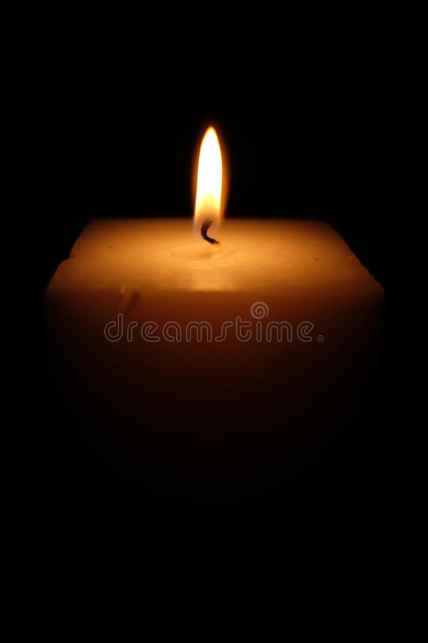 The candle burning in the dark. On a blackbackground stock image