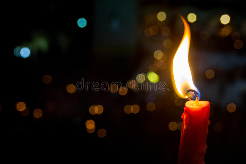 A Candle Burns On A Green Background Of Christmas