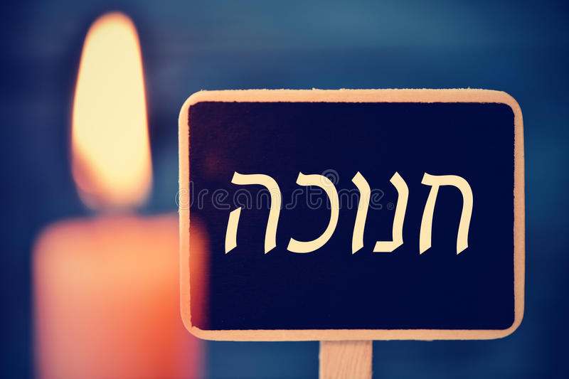 Candle and chalkboard with the text Hanukkah in Hebrew royalty free stock image