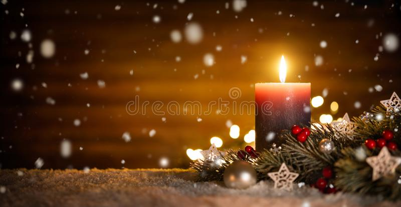 Candle and Christmas decoration with wooden background and snow royalty free stock photos