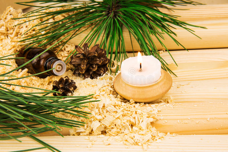 Candle, cones, glass bottle of oil, wooden sawdust, pine twigs a. Macro view of candle, cones, glass bottle of oil, wooden sawdust, green pine twigs and logs royalty free stock images