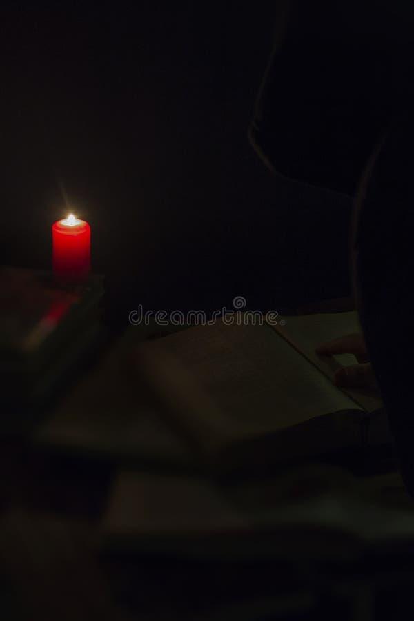 Candle e um livro da Bíblia no fundo de madeira na noite foto de stock