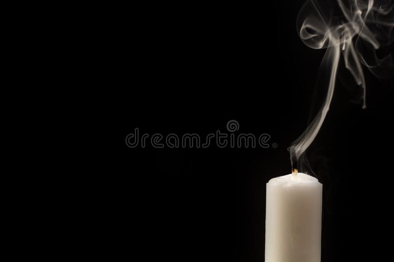 Candle with extinguished flame in front of black background stock photography