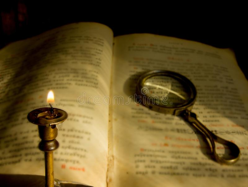 A dying candle and an old prayer book with a magnifying glass stock photos