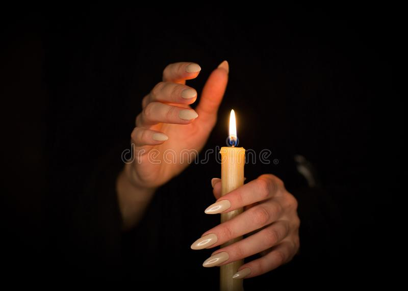 Candle and female witch hands with sharp pearl nails. Divination and witchcraft, low key. royalty free stock images