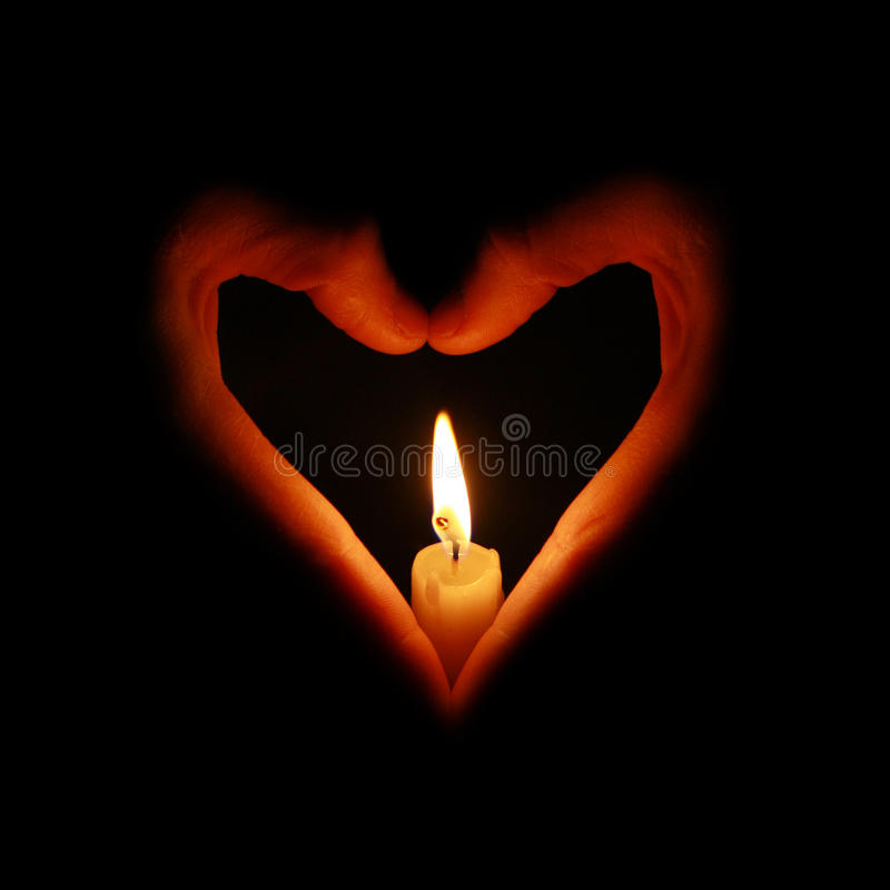 Candle fire in heart-shaped hands