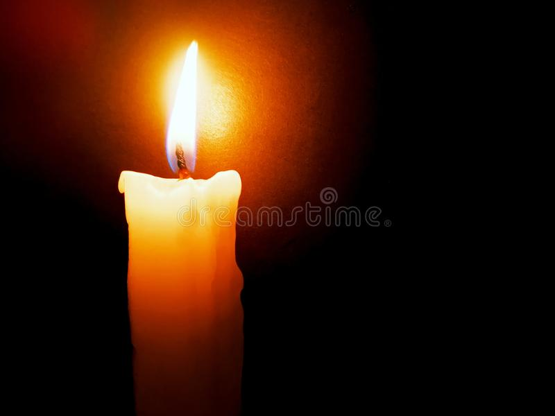 Candle flame close up on a black background stock photography