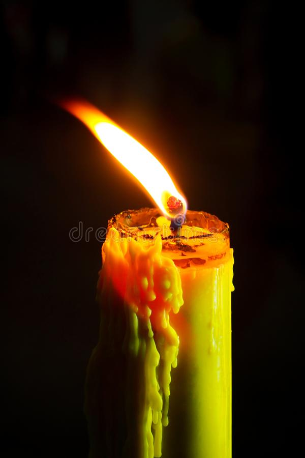 Candle flame close up on a black background. Single light flame candle or beeswax candle burning brightly on black background royalty free stock photos