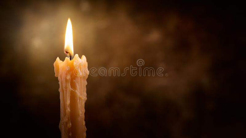 Candle flame close up on a dark background. Candle light border design. Melted Wax Candle Burning at Night. White Candles Burning in the Dark. Candlelight royalty free stock photography