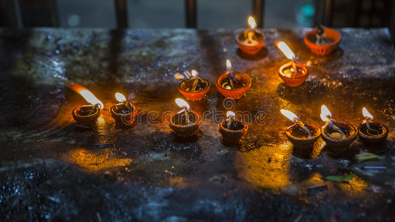 Candle flame close-up in the Indian Temple on a Religious Festival Diwali. Oil Lamp stock photo