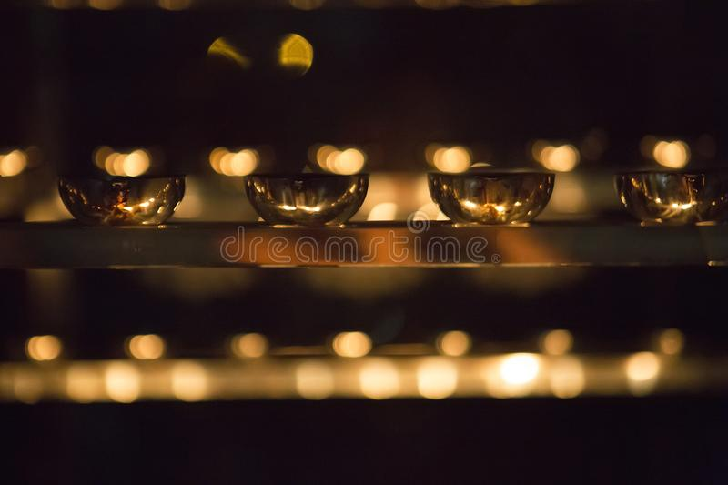 Candle flame close-up. Many Candles in a Buddhist temple. Religious Festival. Oil Lamp royalty free stock photos