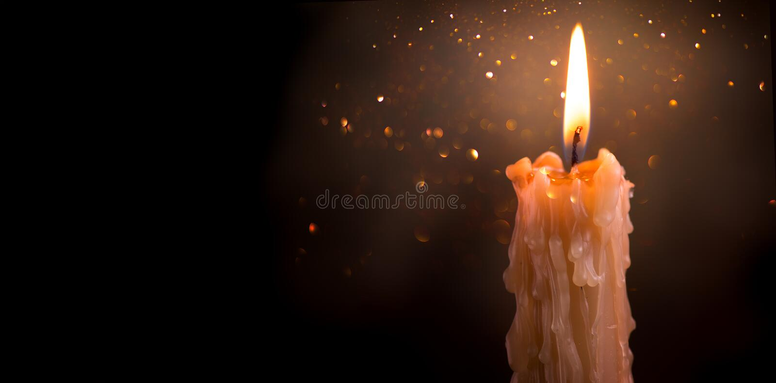 Candle flame closeup on a dark background. Candle light border design. Melted wax candle burning at night. Widescreen stock photography