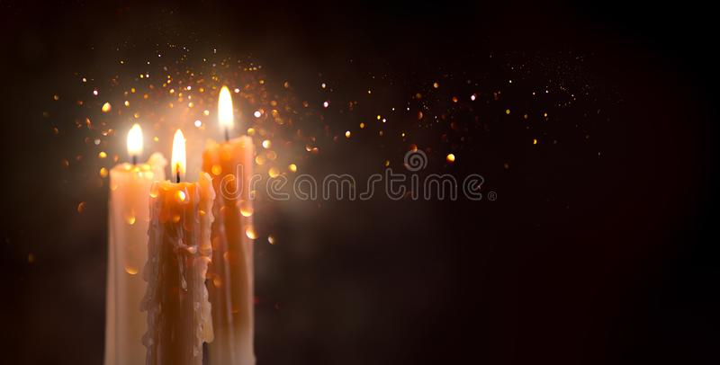 Candle flame closeup on a dark background. Candle light border design. Melted wax candles burning at night stock photos