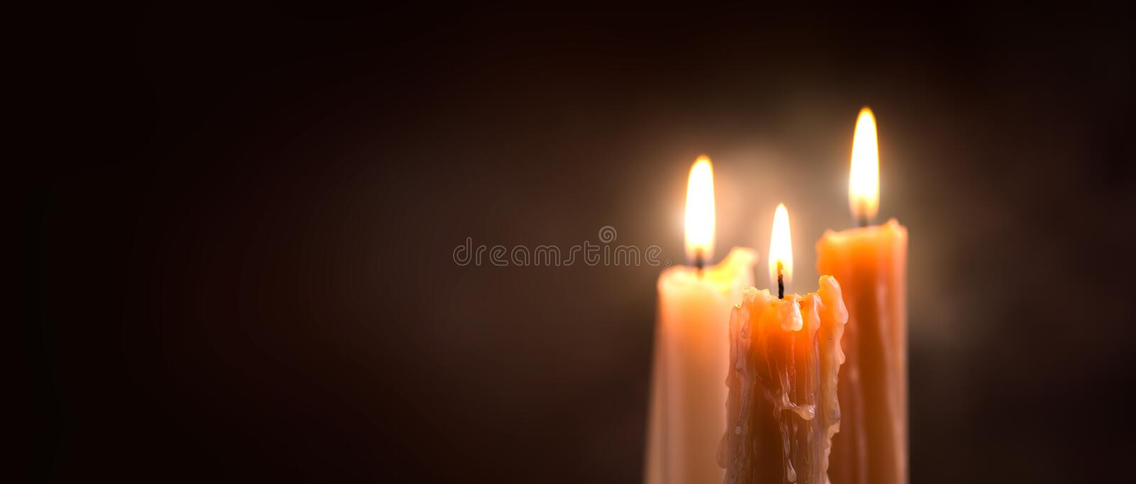 Candle flame closeup on a dark background. Candle light border design. Melted wax candles burning at night. Widescreen stock image