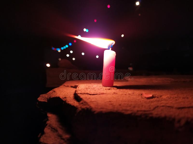 A CANDLE FLAME GIVE LIGHT IN DARK NIGHT WITH LIGHTING BEHIND royalty free stock images