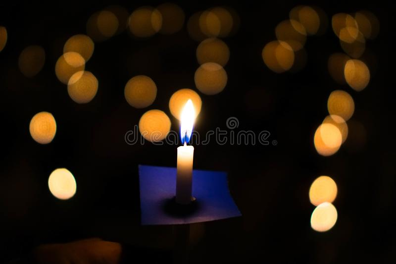 Candle flame at night with bokeh on dark background with go light Blessed is the light of holiness and miracles. royalty free stock photo