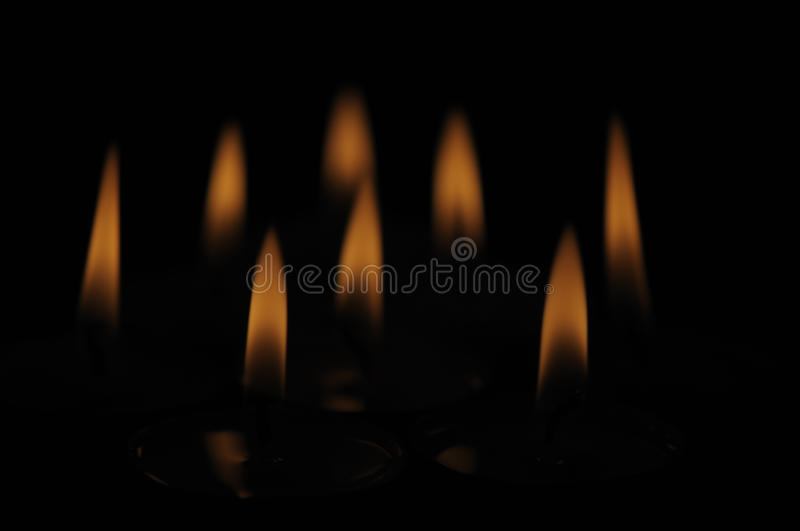 Candle flames isolated over black. Group of several candle flames isolated over black background stock photo