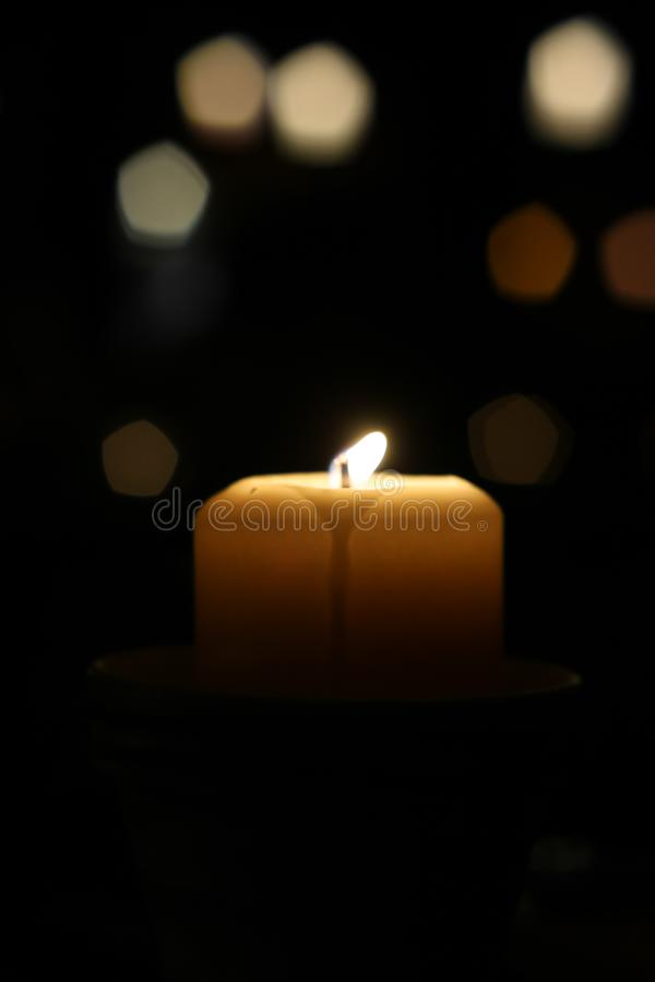A candle flickers brightly on a dark night royalty free stock photography