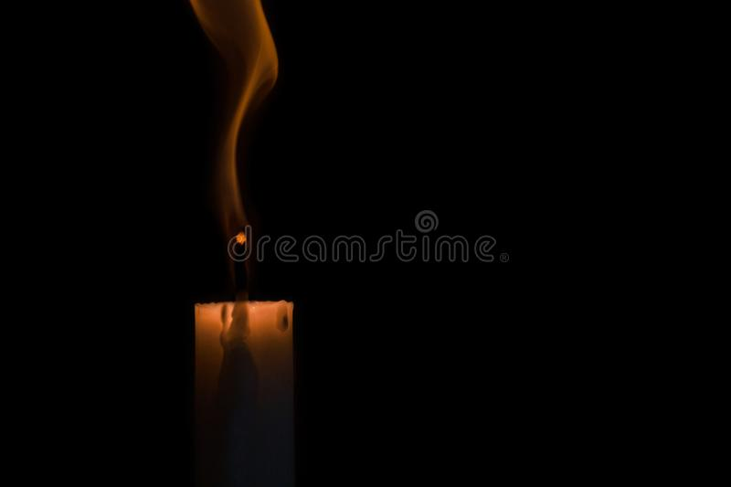 The candle goes out at black background. Close up portrait of the candle goes out at black background with copy space stock image