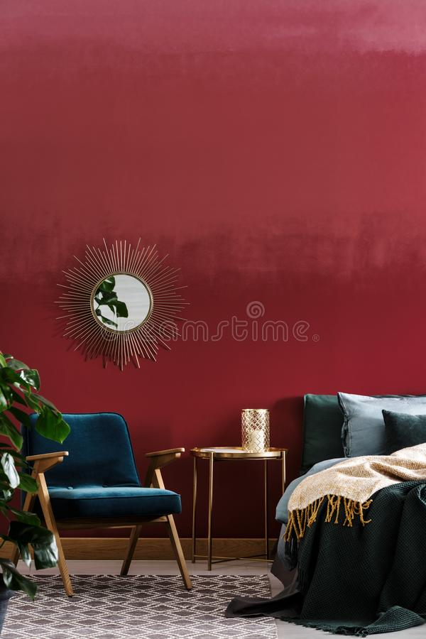 Candle on golden bedside table. Candle placed on a golden bedside table and decorative mirror hanging on a burgundy wall in bedroom interior royalty free stock image