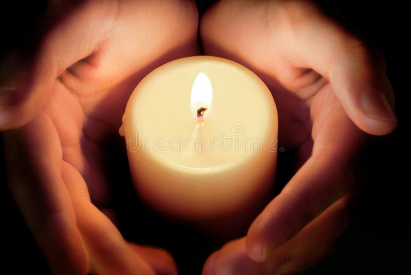 Candle between the hands stock photo